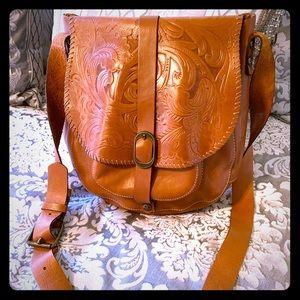 A brandy leather cross body bag by Patricia Nash